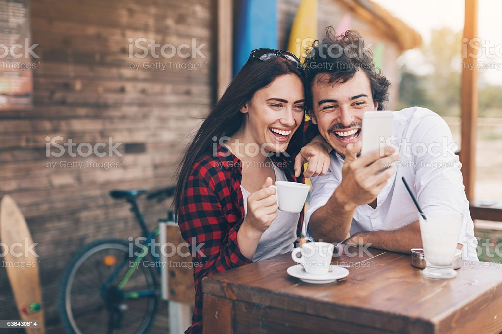 Friends with smart phone in cafe outdoors stock photo