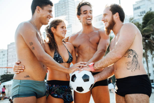 Friends with Soccer Ball holding hands in unity, Rio de Janeiro, Brazil stock photo