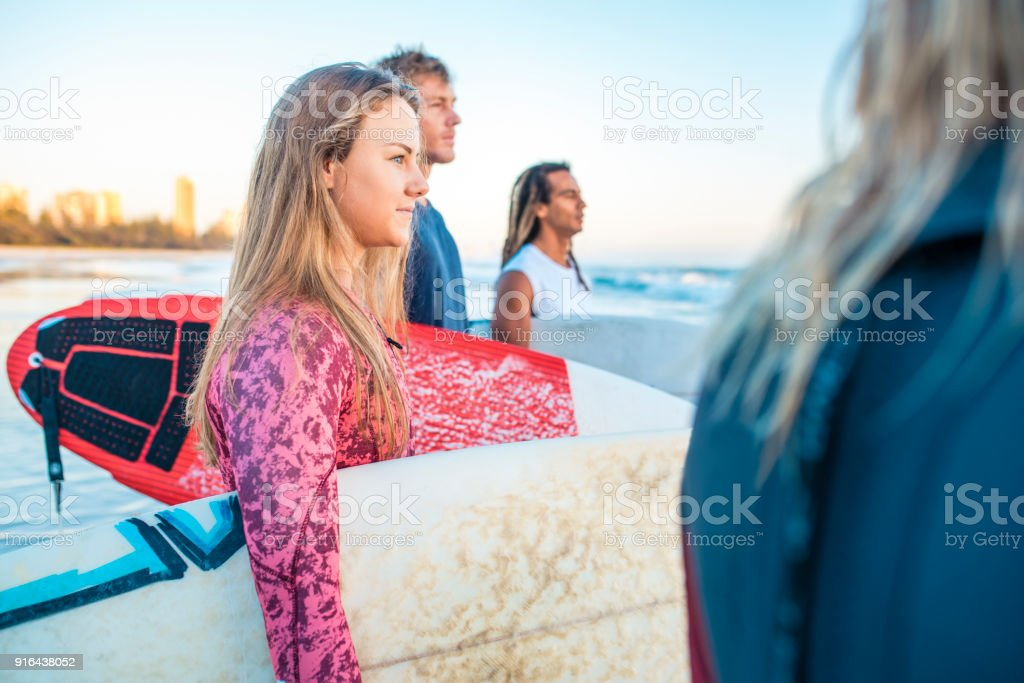 Friends with surfboards standing at the beach stock photo
