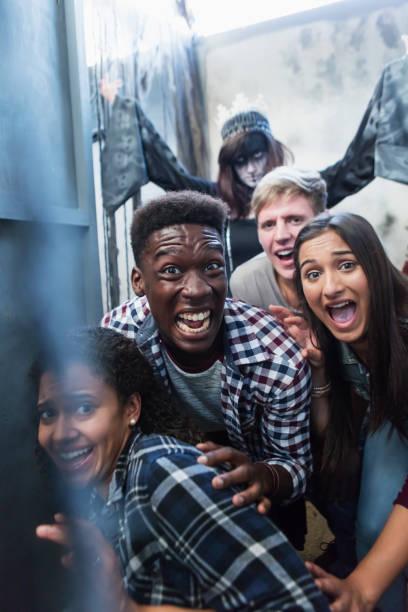freunde mit zombie in halloween geisterhaus - freund kostüme stock-fotos und bilder