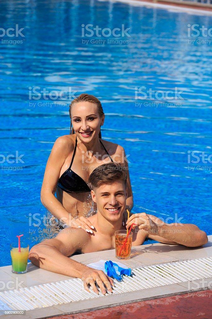Friends Young man and woman couples relaxing at swimming pool royaltyfri bildbanksbilder
