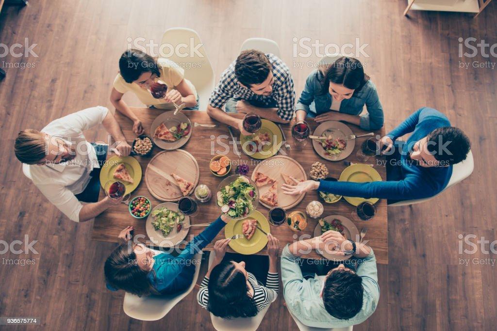 Concepto de amistad y comunicación. Vista superior del grupo de ocho amigos felizes tener buena comida y bebidas, disfrutando de la fiesta y comunicación - foto de stock