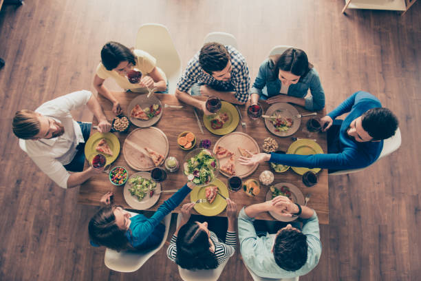 concept d'amitié et de la communication. vue de dessus du groupe de huit amis heureux ayant la bonne nourriture et boissons, profitant du parti et la communication - diner entre amis photos et images de collection