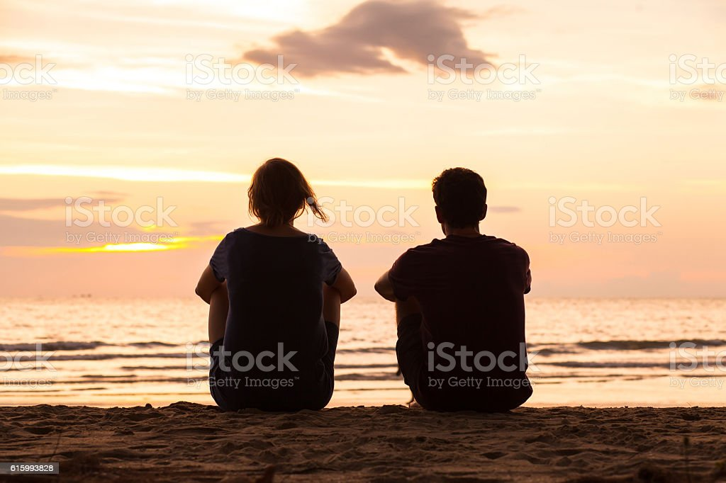 friendship, friends sitting together on the beach stock photo
