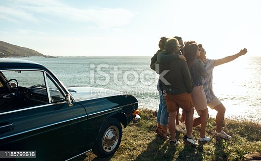 Shot of a group of happy young friends taking selfies on a road trip along the coast
