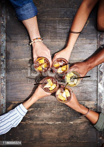 Cropped high angle shot of a group of friends toasting with their drinks at a restaurant