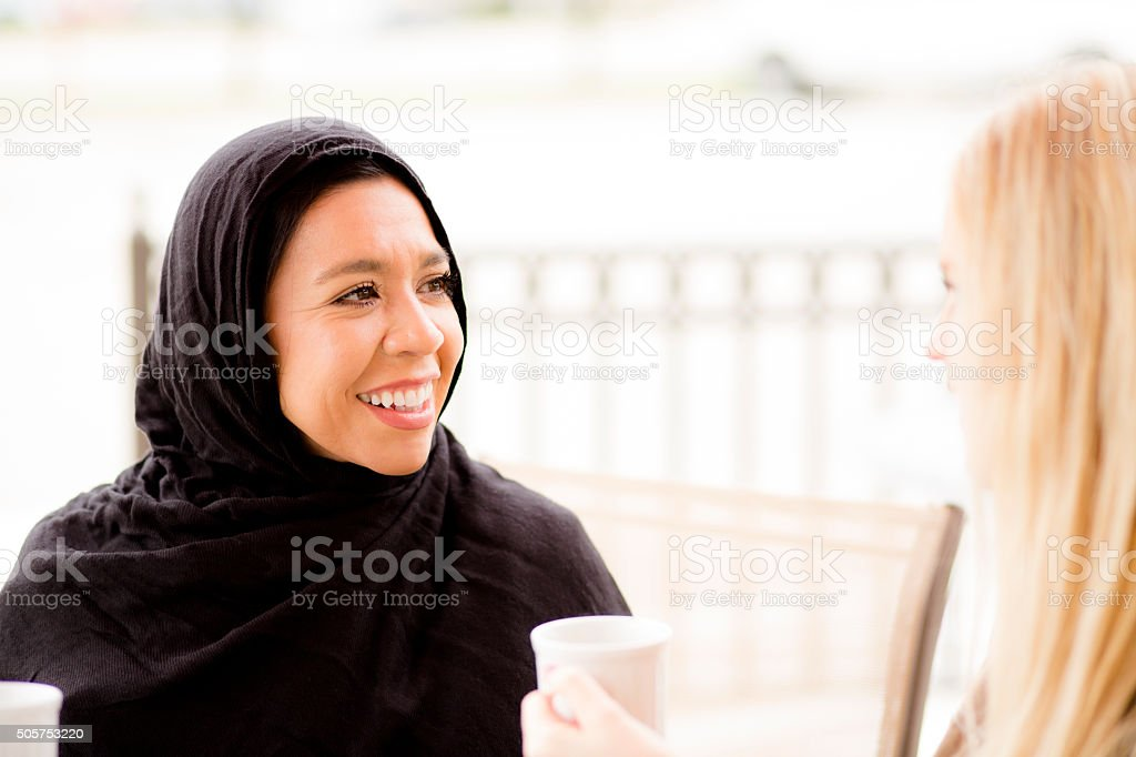 Friendship.  Muslim woman and her friend enjoy coffee together. stock photo
