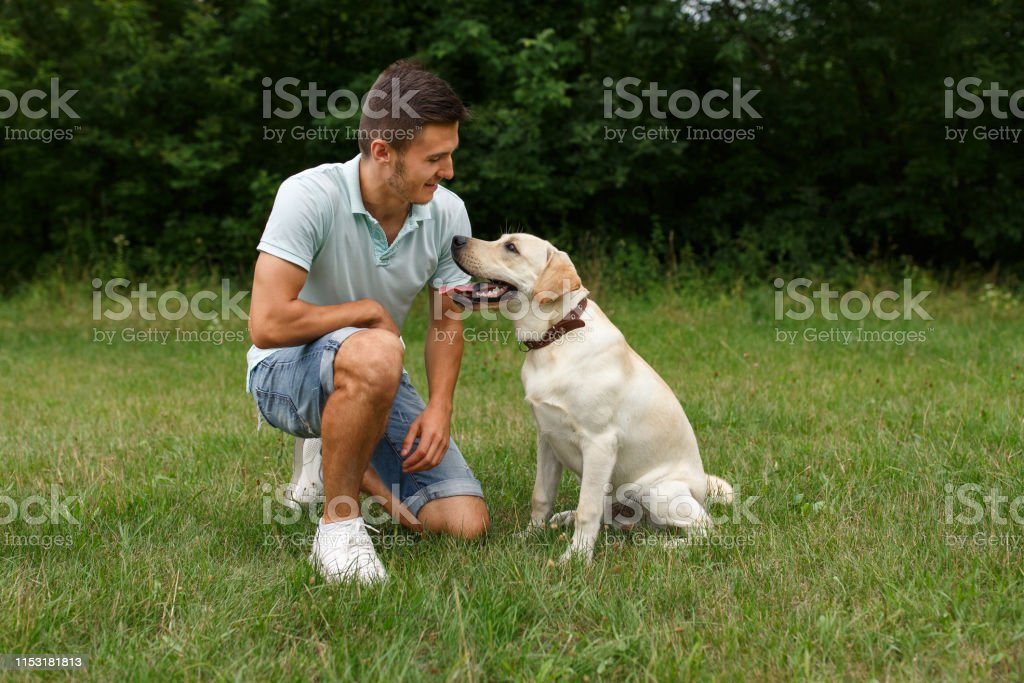 Friendship of man and dog. Happy young man sitting with his friend -...