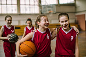 Cute teenage girls, smiling and hugging after basketball match, happy after winning the game