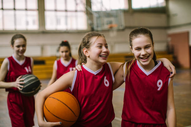 Friendship on basketball court Cute teenage girls, smiling and hugging after basketball match, happy after winning the game pre adolescent child stock pictures, royalty-free photos & images