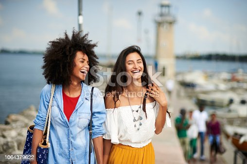 Horizontal picture of two girl friends walking and laughing