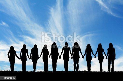 Silhouette of ten young women, walking hand in hand.