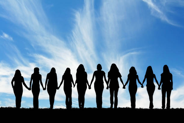Friendship Silhouette of ten young women, walking hand in hand. sister stock pictures, royalty-free photos & images