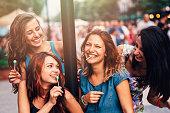 Four beautiful girls licking lollipops.