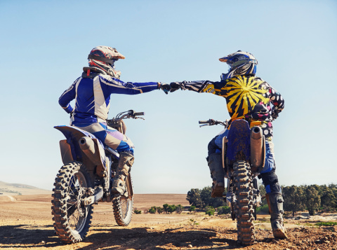 Two motocross riders bumping fists before a race