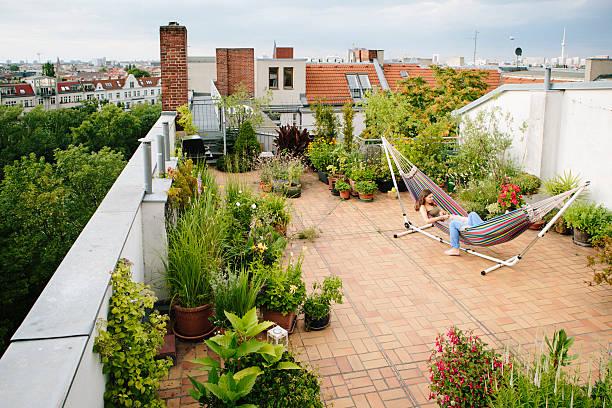 freundschaft: zwei junge frauen entspannen sie im der hängematte, reden - dachgarten stock-fotos und bilder