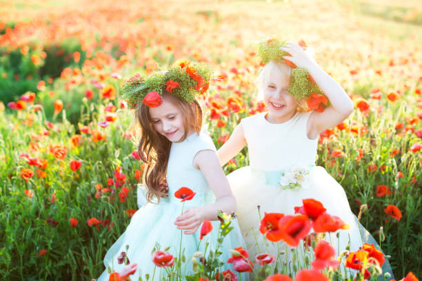 freundschaft, hochzeit, party, freiheit, kindheit konzept - kleine entzückende vettern, ärmellose kleider in verschiedenen farben und große kränze tragen, abholung mohn und lachen - hochzeitsfeier mit kindern stock-fotos und bilder
