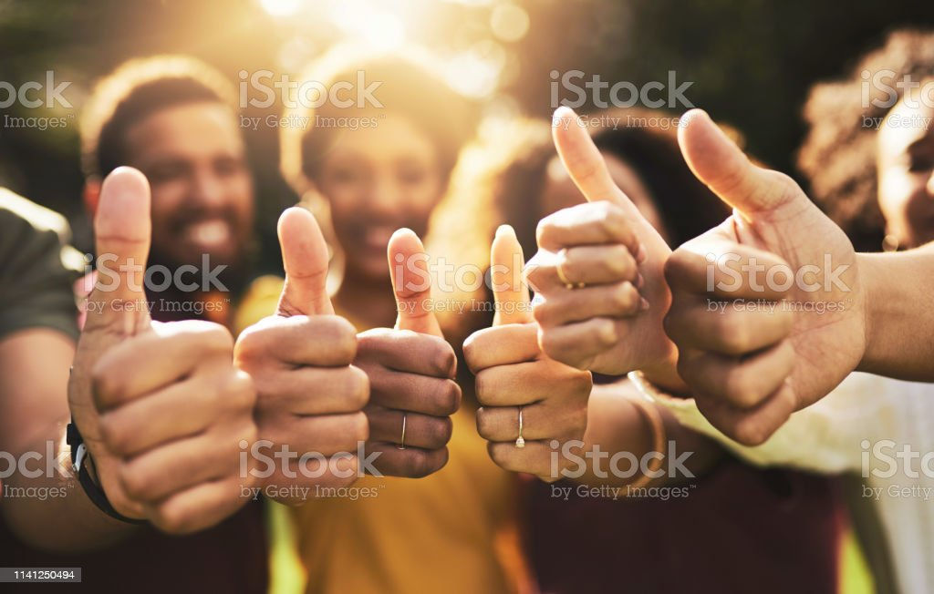 Friendship will turn that frown upside down Cropped shot of a group of friends showing thumbs up 20-29 Years Stock Photo