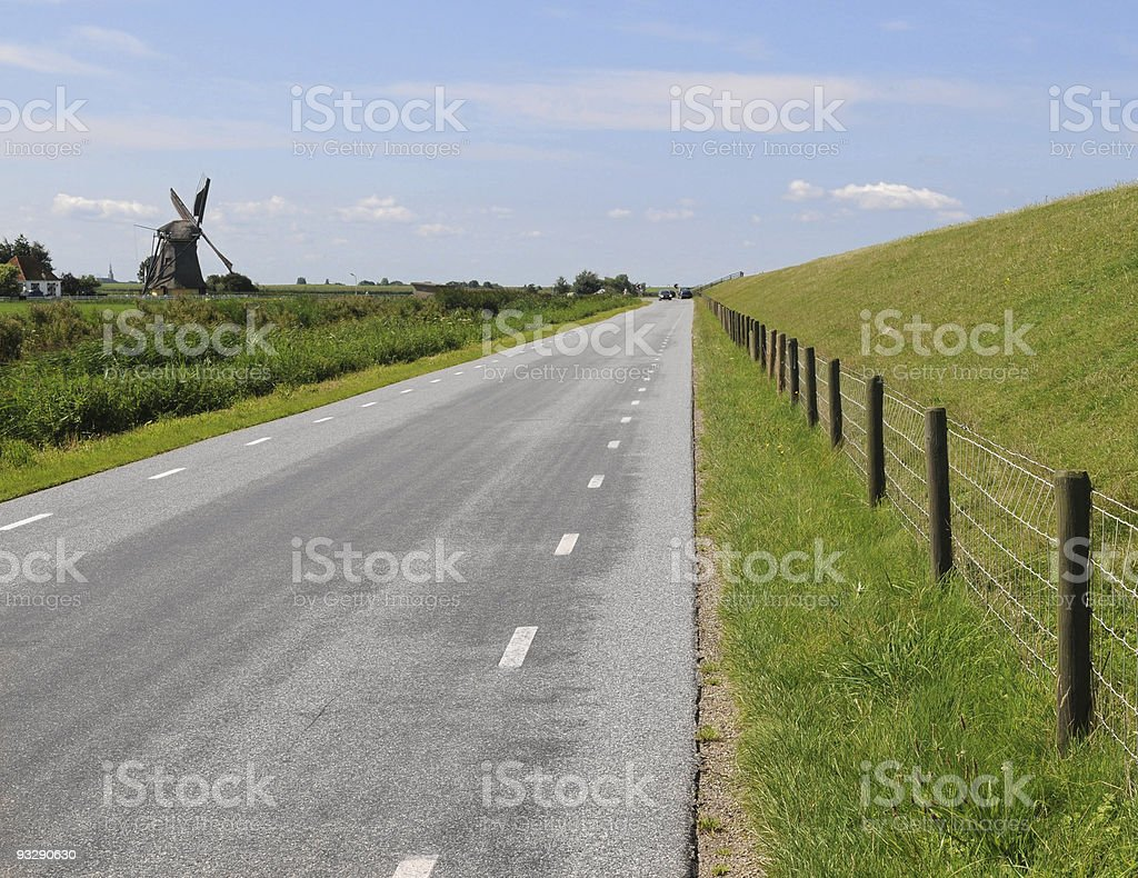 Friesland: straight lines, dike and windmill stock photo