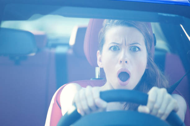 Fright face woman driving car, wide open mouth eyes, strongly squeezing wheel stock photo