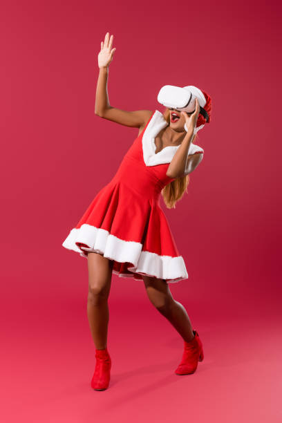 frightened african american girl in christmas dress gesturing while using vr headset on red background - vr red background imagens e fotografias de stock