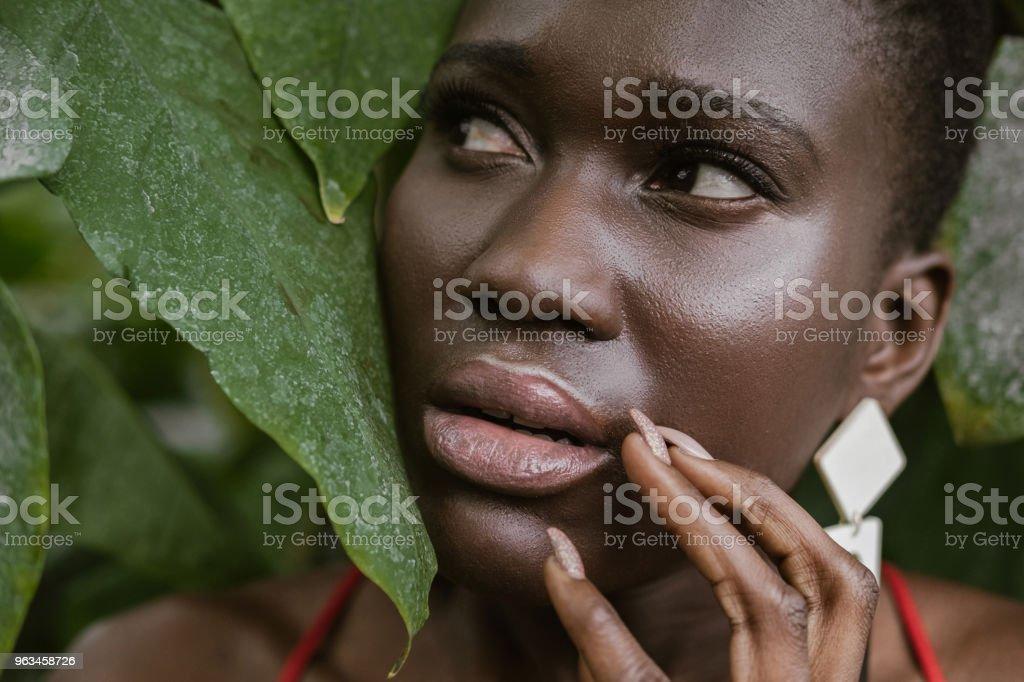 peur femme afro-américaine qui pose en jardin verdoyant - Photo de A la mode libre de droits