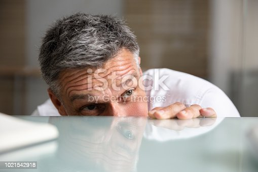 Close-up Of A Frightened Businessman Peeking From The Edge Of Reflective Desk