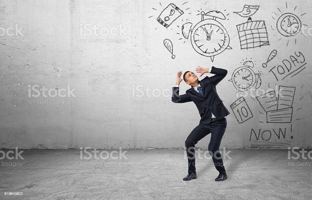 Frightened businessman shielding himself with his hands from the drawings A frightened businessman shielding himself with his hands from the drawings of calendars and clocks on the grey wall. Business and time-management. Organizing and planning. Productivity and efficiency. Adult Stock Photo