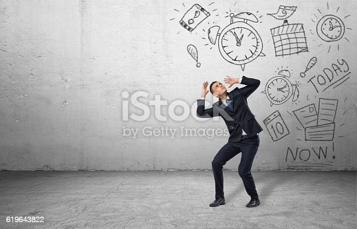 istock Frightened businessman shielding himself with his hands from the drawings 619643822