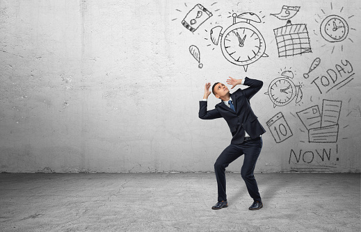 Frightened Businessman Shielding Himself With His Hands From The Drawings Stock Photo - Download Image Now