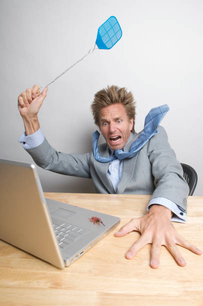 Frightened Businessman Swatting Bug on Computer  computer bug stock pictures, royalty-free photos & images
