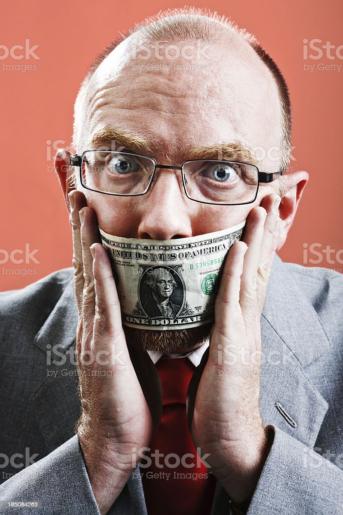 Frightened businessman tries to remove dollar bill gag stock photo