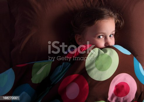 Little girl in her bed, looking very frightened