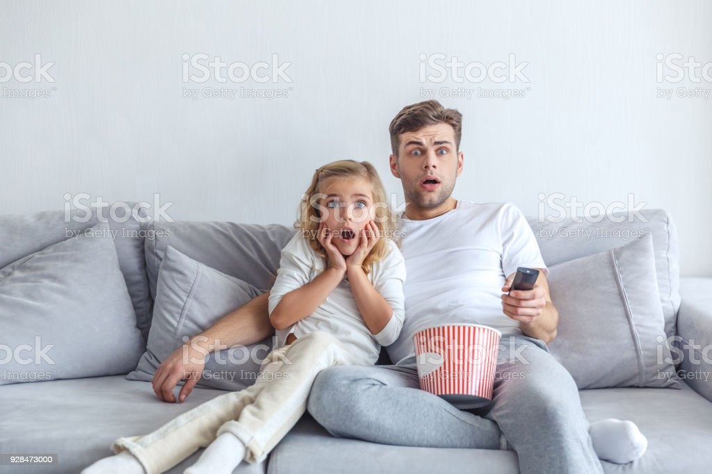 frightened father and daughter watching scarry movie at home stock photo