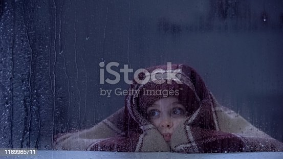 Frightened girl covered in blanket on sill, looking through rainy window, fears