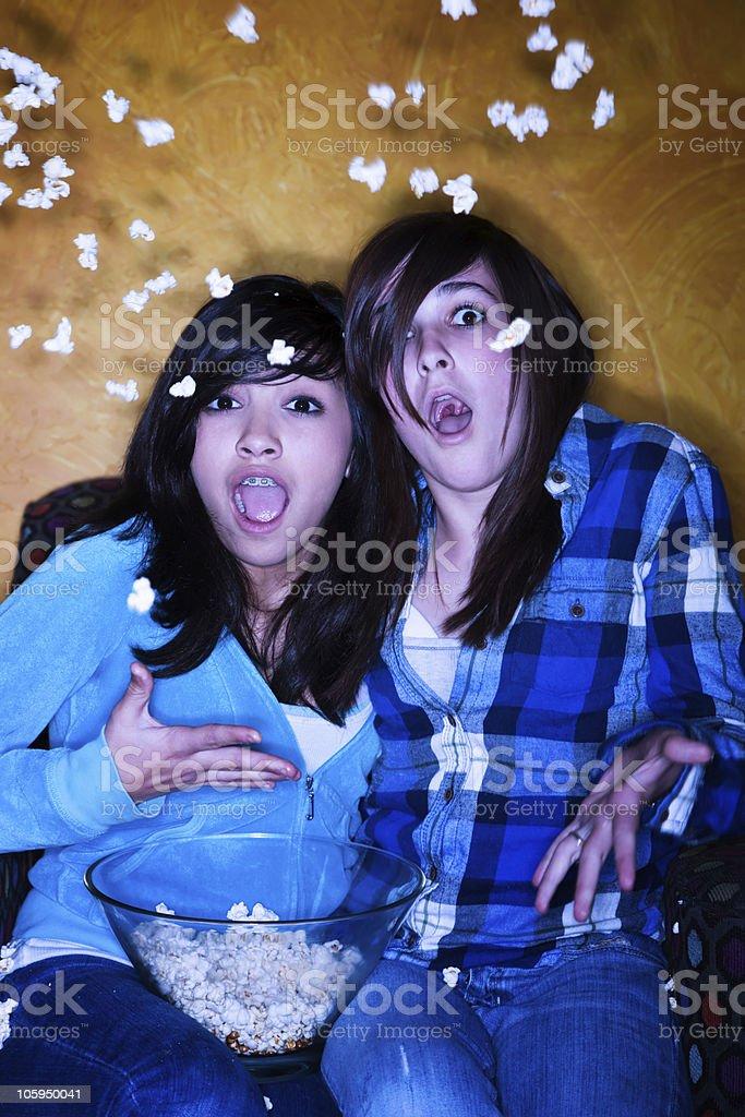 Frightened Hispanic girls with popcorn watching television royalty-free stock photo