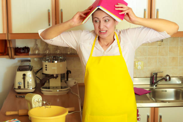 frightened housewife with cookbook on head - fail cooking imagens e fotografias de stock