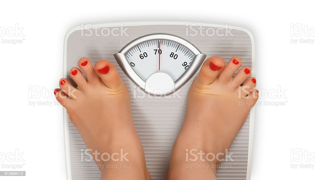 Frightened legs on bathroom scale stock photo