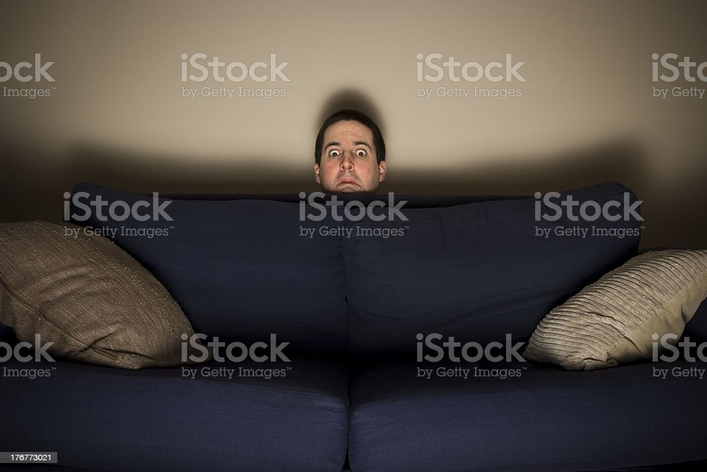 Frightened man peeks over a couch while watching TV stock photo