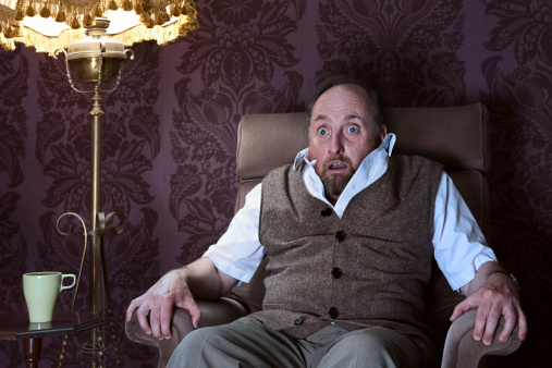 Frightened man sitting on an arm chair and watching a horror movie on TV with old fashioned furniture and wall paper.