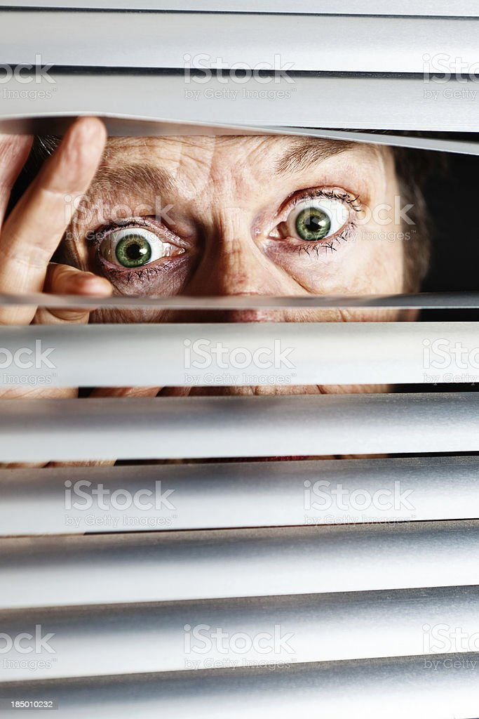Frightened old woman peeps through venetian blinds stock photo