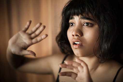 istock Frightened teenage girl looking away and hiding herself behind hands. 496875650