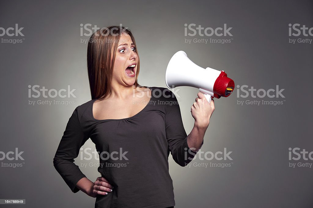frightened woman looking on megaphone royalty-free stock photo