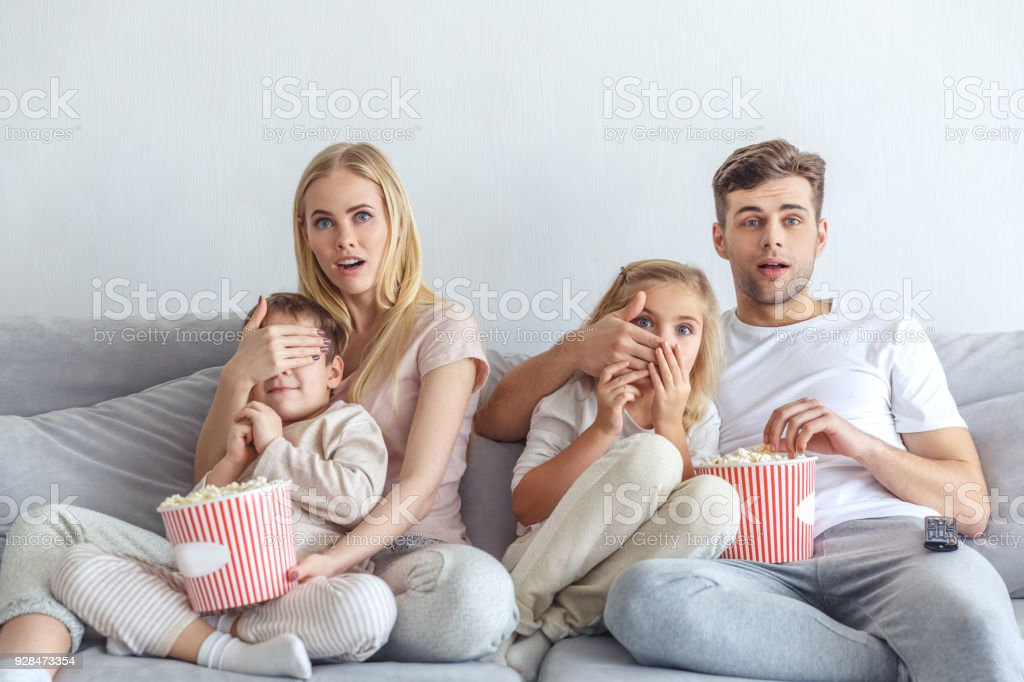 frightened young family watching scarry movie on couch at home stock photo