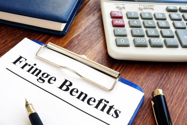 Fringe Benefits documents with clipboard and calculator. stock photo