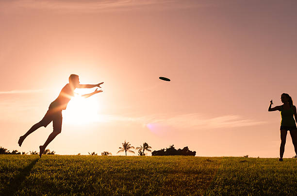Frisbee Couple playing frisbee game in the park. plastic disc stock pictures, royalty-free photos & images