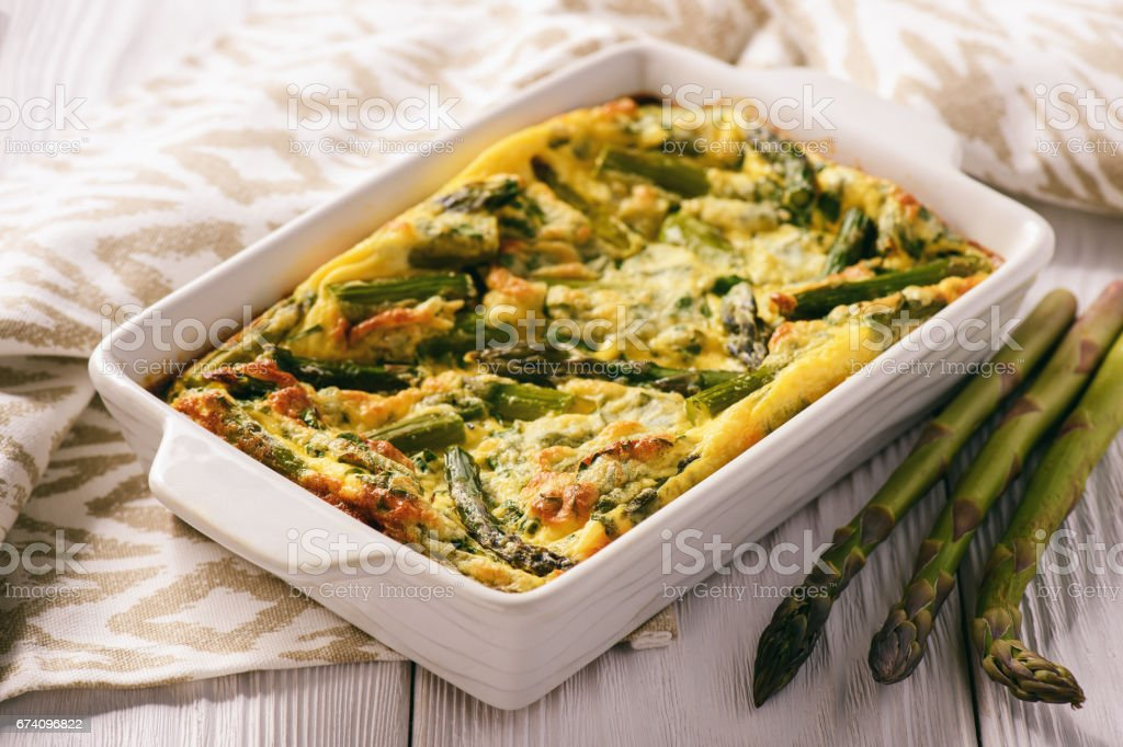 Fritata with asparagus on wooden background. stock photo