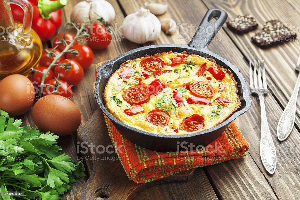 Frittata in cast iron skillet on a wood surface stock photo