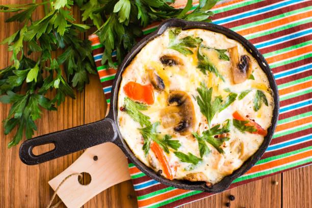 Yumurta, domates, mantar, tavuk ve peynir bir kızartma tavası ve taze maydanoz ahşap bir masa üzerinde yapılan frittata stok fotoğrafı