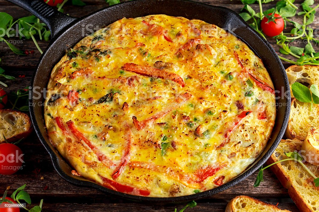 Frittata made of eggs, potato, bacon, paprika, parsley, green peas foto royalty-free